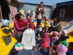 Kinder und Betreuerinnen spielen und singen