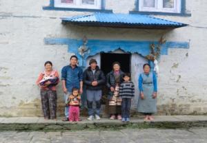 """Familie Phemba Lamu Sherpa vor ihrem als """"Fully damaged"""" klassifizierten Haus; dieses ist eines der vier Häuser, das in der nun beginnenden Bauperiode abgetragen und neu aufgebaut werden muß. Die Familie hat schon viele Monate in einer nahegelegenen Notunterkunft verbracht"""